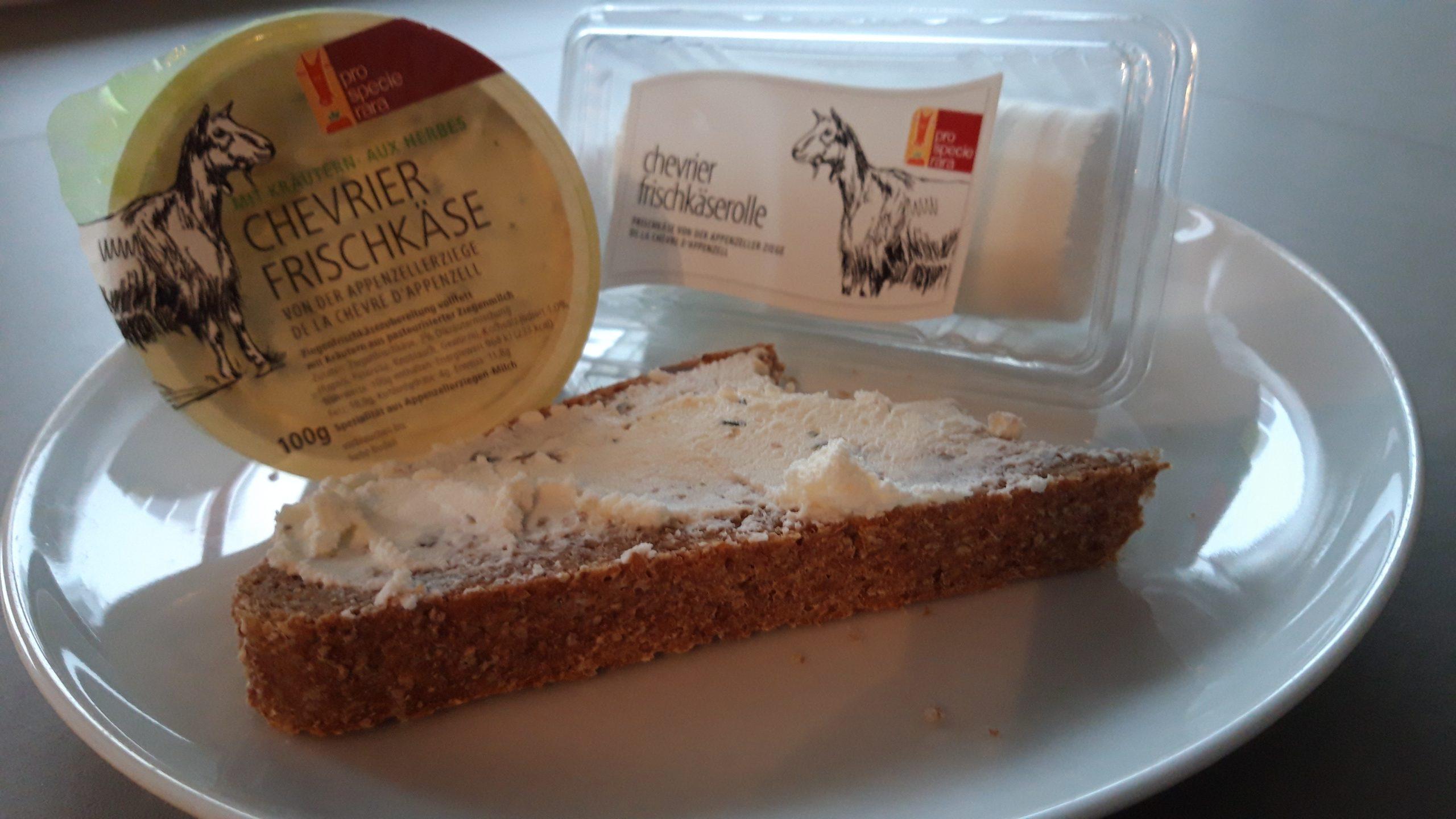 Stück Brot mit Frischkäse mit Kräutern der Appenzeller Ziege auf weissem Teller mit zwei Sorten Ziegenfrischkäse in Originalverpackung