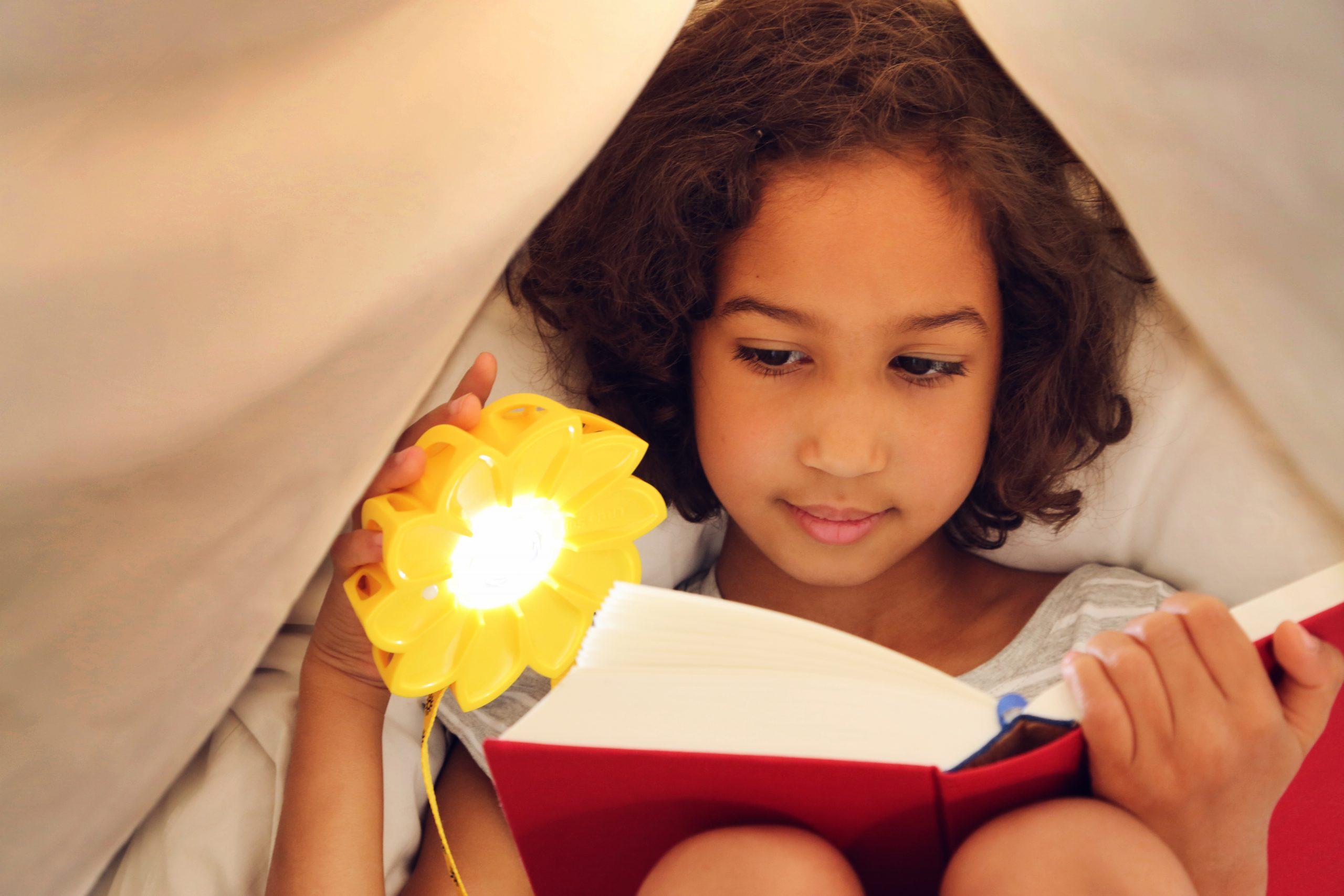 Kind in Zelt beim Lesen mit Solarlampe little sun