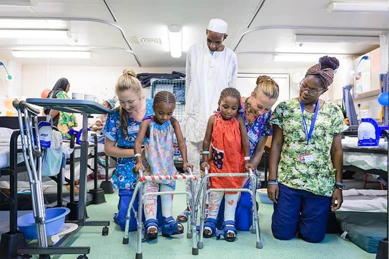 Zwei afrikanische Mädchen lernen mit Rollatoren gehen nach einer Beinoperation