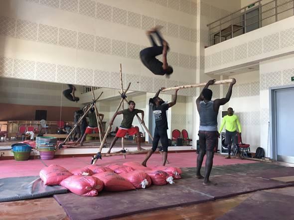 In einer Halle halten zwei Jugendliche eine Stange, über die ein dritter einen Salto macht. Am Boden liegen Matten und rote, gefüllte Plastiksäcke als Schutz..