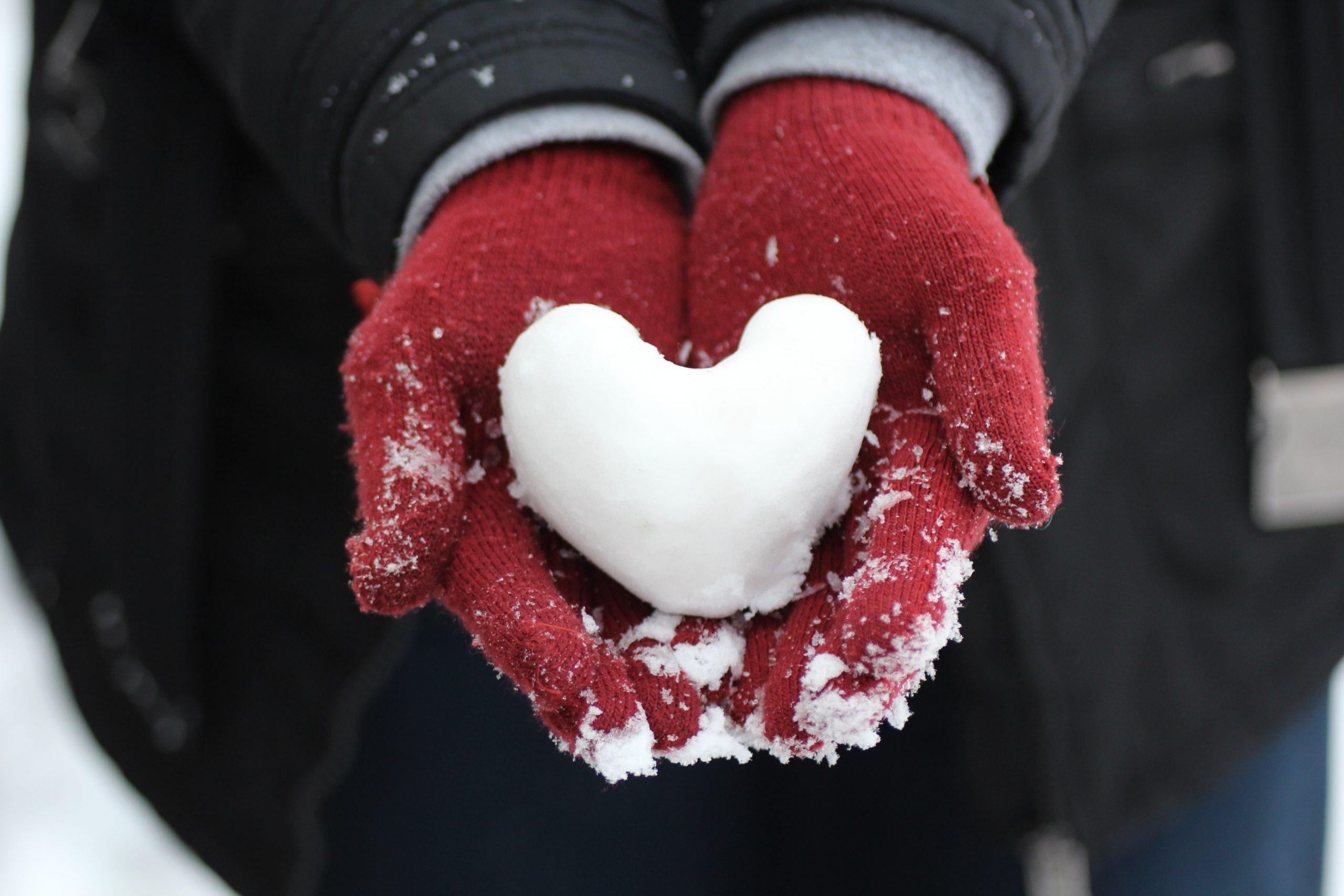 Herz aus Schnee in behandschuhten Händen