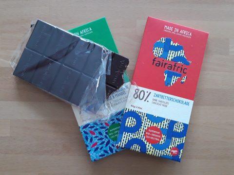 Zwei Tafeln dunkle Fairafric-Schokolade auf Holztisch, eine ausgepackt und angebissen