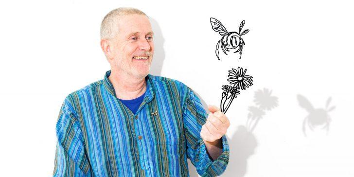 Mann mit einer gezeihneten Bienenpflanze in der Hand und einer Biene