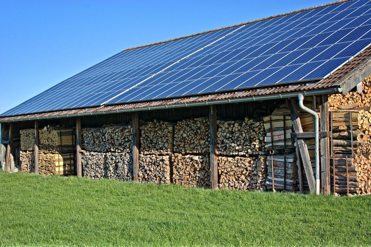 Scheune mit viel gestapeltem Brennholz und Photovoltaik auf dem Dach