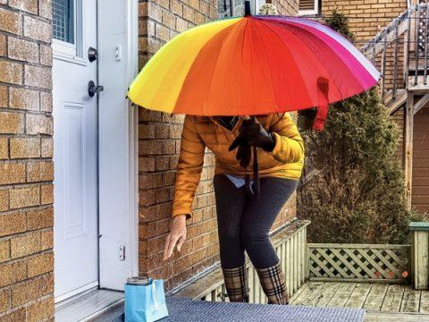 Frau mit Schirm legt etwas vor Türe des Nachbarn