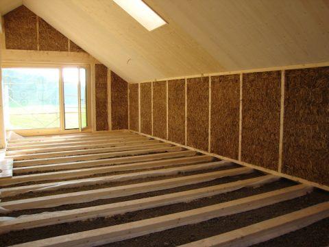 Bau eines Hauses aus Holz, isoliert mit Stroh und verputzt mit Lehm
