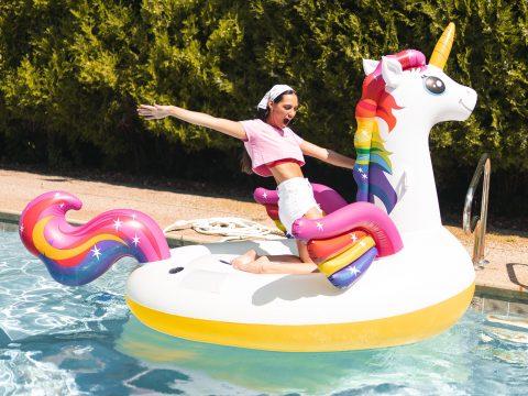 Mädchen auf Aufblas-Einhorn im Pool