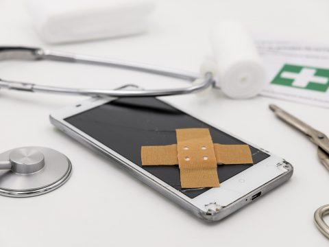 Symbolbild für Handyreparatur: Handy mit zwei Pflastern über Kreuz auf Display, drum herum Stethoskop, Schere und Gaze