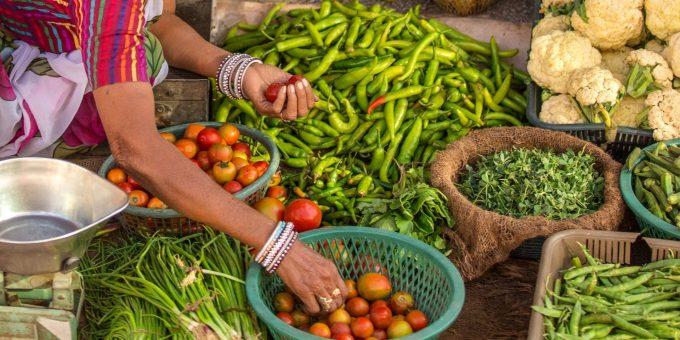 Frauenhände über tropischem Gemüse auf einem Markt