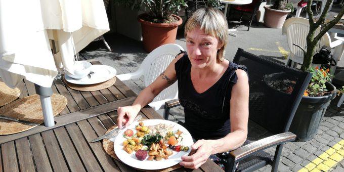 Frau am Tisch mit gemischtem Teller vom Buffet an einem Tischim Aussenbereich des veganen Restaurant Sacred.