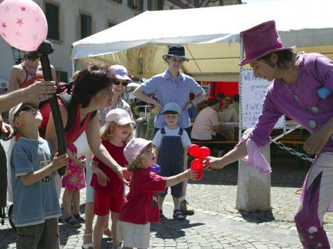 Gaukler in violett-weisser Kleidung mit Hut schenkt Kleinkind ein rotes Ballontier unter den Augen der Mutter und einer etwas älteren Schwester, während der ältere Bruder sein Ballongeschenk bewundert mit dem Vater