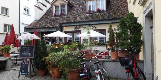 """Blick auf """"Annegreth's Schützenstube"""" in Schaffhausen mit Terrasse mit Sonnenschirmen und Kübelpflanzen; im Vordergrund drei parkierte Velos"""