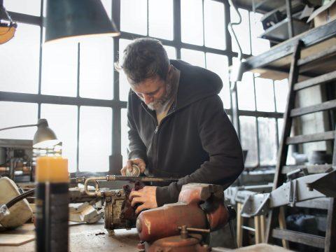 Mann bei einer Reparatur in einer Werkstatt
