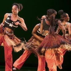 Vier afrikanische Tänzerinnen im Kreis mit orangen Hosen, Baströcken und schwarzen, mit Muscheln besetztem Bustier