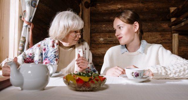 Seniorin hört sich die Sorgen eines Mädchens an beim Tee