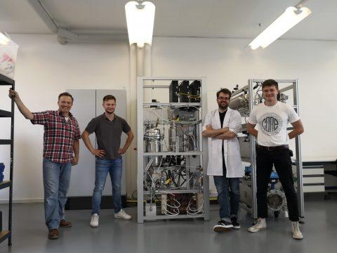 Das Team - vier Männer - vor Prototyp des Bioreaktors der Firma Methanology