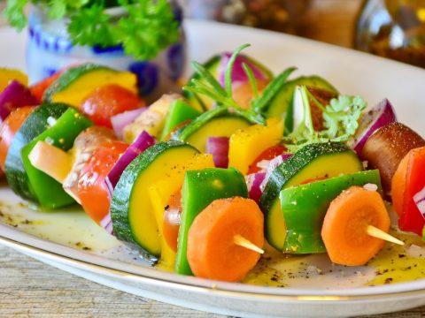 Drei Gemüsespiessli mit Rüebli, Peperoni, Zucchetti, roten Zwiebeln und Champignon auf weissem, ovalem Teller mit Marinade darüber